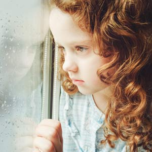 Young Child With Developmental Trauma Disorder At Window
